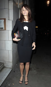 Helena dons a one-button cardigan sweater over a black and white sheath dress while leaving her London hotel.