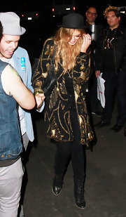 Delta Goodrem contrasted her glam coat with a pair of edgy black lace-up boots.