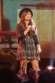 Demi Lovato performed at the El Capitan Theater in a black and olive print dress toughened by an open leather jacket.