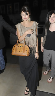 Selena Gomez gave her casual dinner attire a classic finish with a tan printed MCM Heritage Line bowler bag.