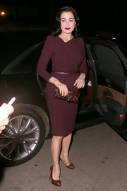 Dita Von Teese chose this burgundy cocktail dress with peak sleeves and a cinched waist for her retro evening look.