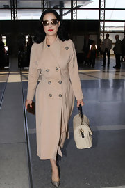 Dita Von Teese rocked her classic retro style while traveling when she wore this structured tan trench with embellished buttons.