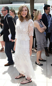 Elizabeth Olsen pared down her long lacy dress with black bow-adorned thong sandals.