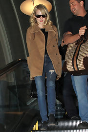 A sand-colored wool coat topped off Emma Stones casual and comfy travel look.
