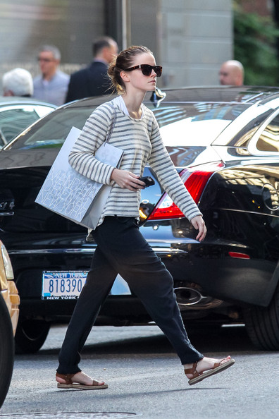 Emma Watson finished off her strolling getup with a pair of flat brown sandals.
