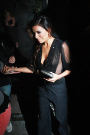 Eva arrived at her restaurant in this sheer black Swiss-dot blouse.