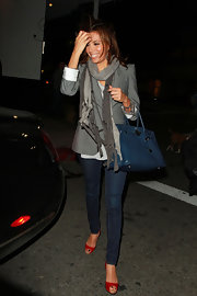 Eva wears a fashionable set of beaded scarves over her blazer and jeans.