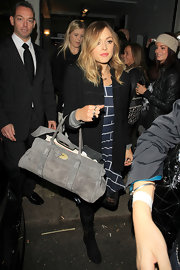 Making her way through the crowd, Fearne showed off a suede tote bag.