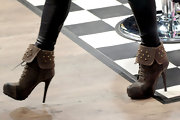 Fergie blended rock star edge with feminine flare when she sported these brown leather, heel booties with gold stud embellishments.