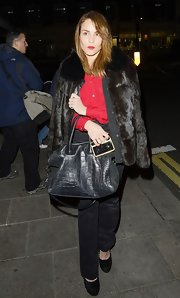 Noomi Rapace glammed up her casual button-down and slacks combo with a black fur coat during a night out in London.