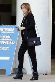 Ellen Pompeo maintained her slick street style with a black woven purse and wedge booties.
