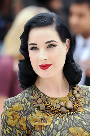Dita's red lips added a pop of color to her muted ensemble.