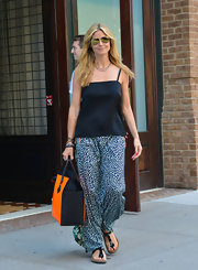 Heidi opted for a loose boho-style look all around when she donned this relaxed black spaghetti-strap top with her printed pants.