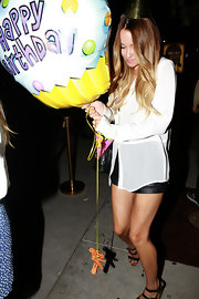 Lauren Conrad celebrated a friend's birthday in style in a sheer white blouse and black leather shorts.
