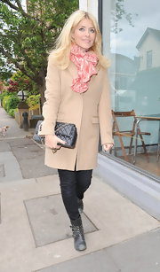 Holly accessorized her classic wool coat with a vibrantly colored pink and peach scarf.