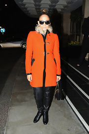 Jennifer Lopez bundled up in a bright orange wool coat with a fur-trim collar.