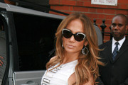 Jennifer Lopez wears a figure hugging white dress as she leaves her London hotel headed for the airport.