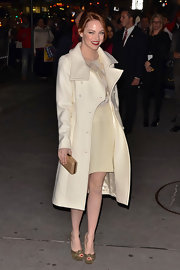 Emma Stone mixed creamy tones in an eggshell wool coat and a beaded ivory dress.