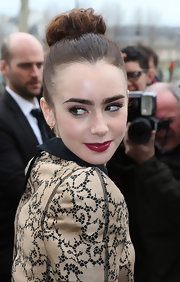 A deep red lip gave Lily Collins a mature beauty look at Paris Fashion Week.