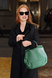 The actress added a pop of color to her look with a green leather tote.