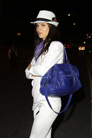 Juliette dons a white fedora with a feather for her bright white ensemble at the opening of 'Organic Liaison.'