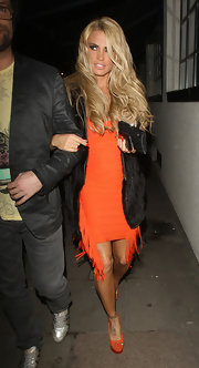 Katie Price tamed her fringed orange dress with a furry black coat.