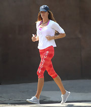 Kelly Bensimon took a jog in NYC wearing this white henley paired with red striped workout pants.