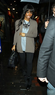 Kelly Rowland dressed up her simple shirt and taupe cardigan with an ornate statement necklace.