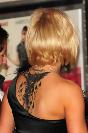 "Kerry shows an artistic design tattoo on her upper back with ""Maxwell"" written above it"