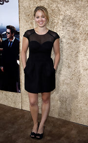 Erika wore a sheer-inset pocketed cocktail dress peep toe pumps. Without accessories, this look was a little dull.