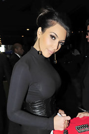 Kim highlighted her high bun with gold and black dangling earrings. It was a nice touch to her long sleeve dress.