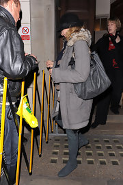 While leaving a theater Kim stops to sign a few autographs for her fans. She was all bundled up in her fury trench coat and grey leather shoulder bag.