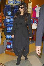 Kim layered up at the airport in a black wrap cardigan and knee-high boots.