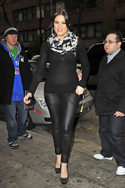 Khloe rocks some skinny leather pants with pockets while out in NYC. She pairs this look with a sheer sweater and black and white print scarf. Don't forget the studded pumps, of course!