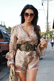 Kim cinched her flowing dress with an oversized, bronze belt.