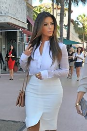 Kim looked like a classic beauty in a simple, slightly-sheer button-down blouse.