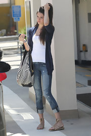 Kendall rolls her well-worn skinny jeans to show off one of summer's hottest trends: the nude gladiator sandal.