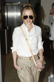 Kylie Minogue paired her white blouse and khaki trousers with a cool cross body bag.