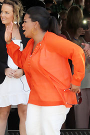 Oprah Winfrey chose an airy orange blouse for her Sydney Harbour cruise.