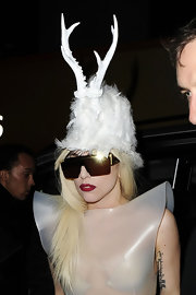 Lady G wears a feathered hat with white deer antlers.