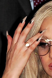 Lady Gaga wore her long stiletto nails painted with a pale polish and dabbed with a spot of black while out in London.