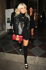 Pixie paired her all black look with a fiery red clutch, which is embellished with gold hardware.