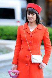 Lea Michele donned this unique red hat with her orange coat and pink suitcase on the set of 'Glee.'