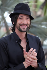 Adrien looks stylish at the Cannes Film Festival in a tilted black fedora.