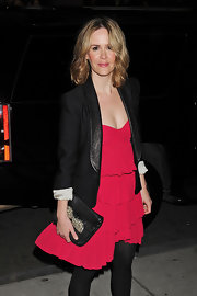 Sarah Paulson added a festive touch to her red dress with a black bow-adorned clutch. A leather trimmed blazer gives her lovely look a masculine edge.