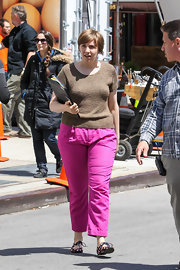Lena kept her look casual with a brown crewneck sweater and bright pink pants.