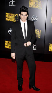 Adam wears a thin black tie to complete this classic formal look.