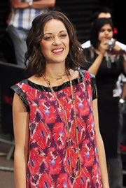 Marion Cotillard styled her print dress with layers of gold necklaces.