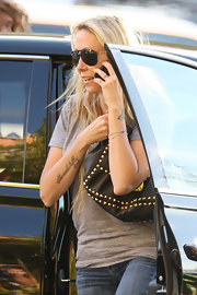 "Miley's mom Tish Cyrus sports a tattoo on her right arm that reads ""She wants to fly"" in cursive script."