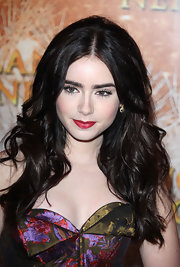 Lily Collins arrived at the premiere of 'Mirror Mirror' wearing a saturated blue-based red lipstick.